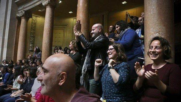 Ciudadanos portugueses aplaudiendo tras la aprobación en el Parlamento portugués